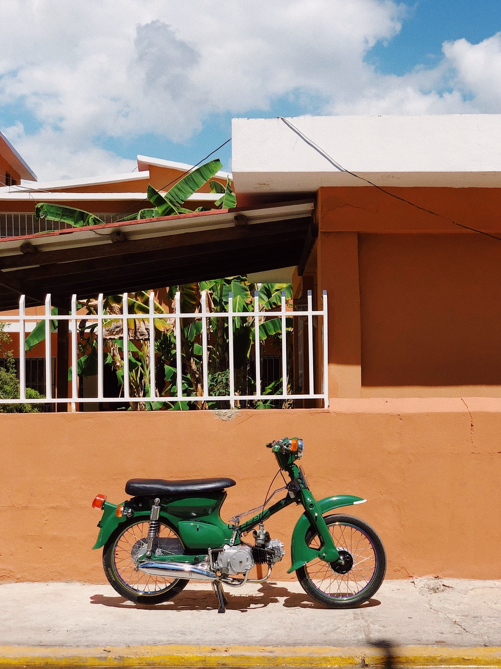 green and black motorcycle parked beside brown concrete building during daytime