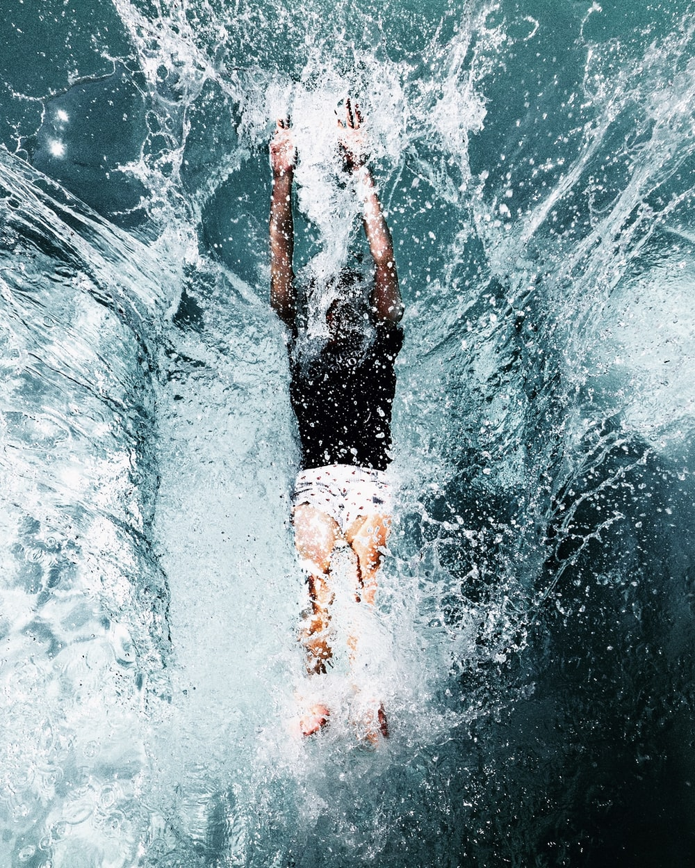 man in black shorts and white shirt in water
