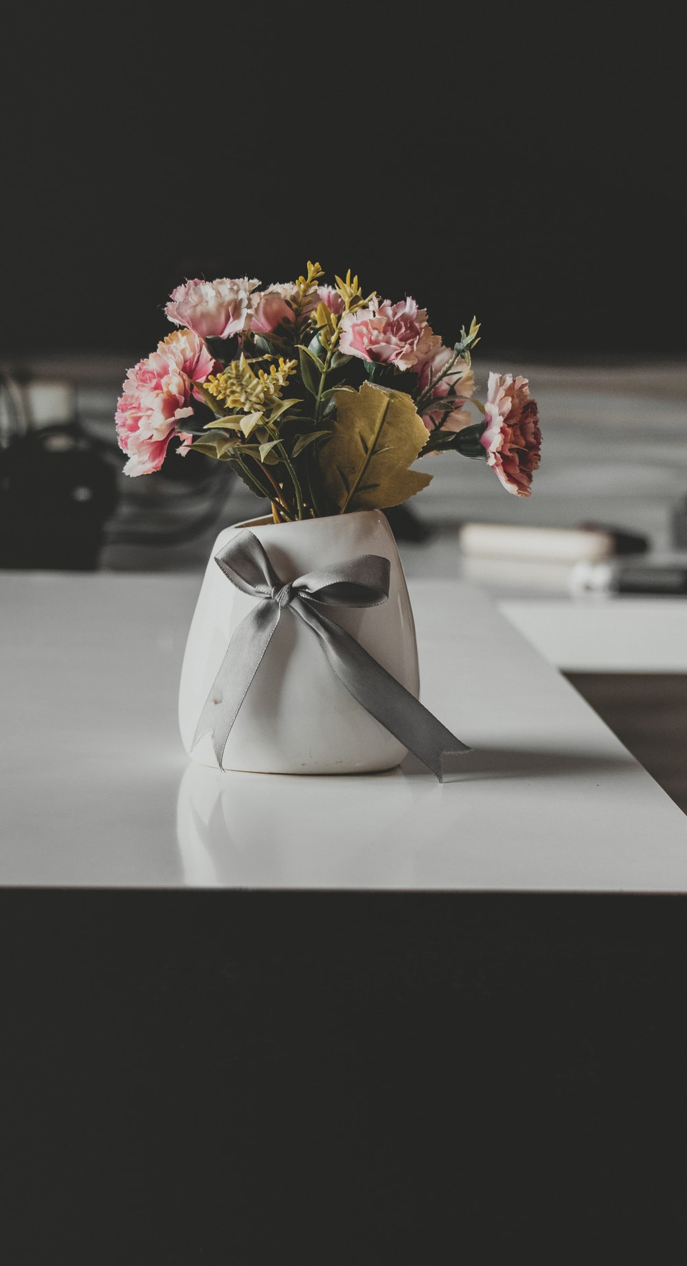 pink and yellow flowers in white vase on table