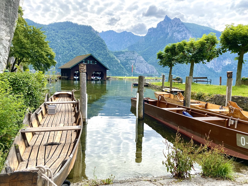 brown wooden boat on water near green trees and mountain during daytime