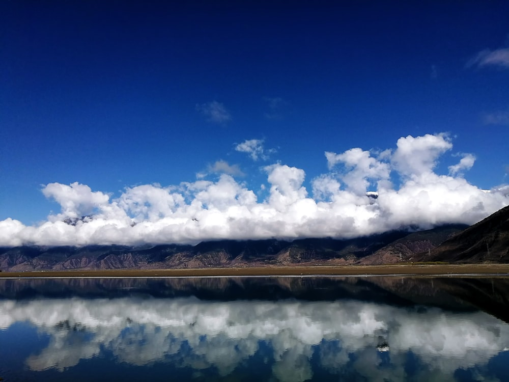 body of water near mountain under blue sky and white clouds during daytime