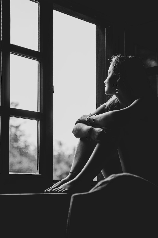 grayscale photo of woman sitting on window