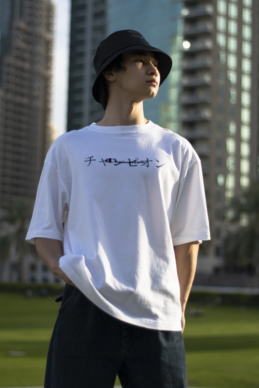 man in white crew neck t-shirt and black pants standing on green grass field during