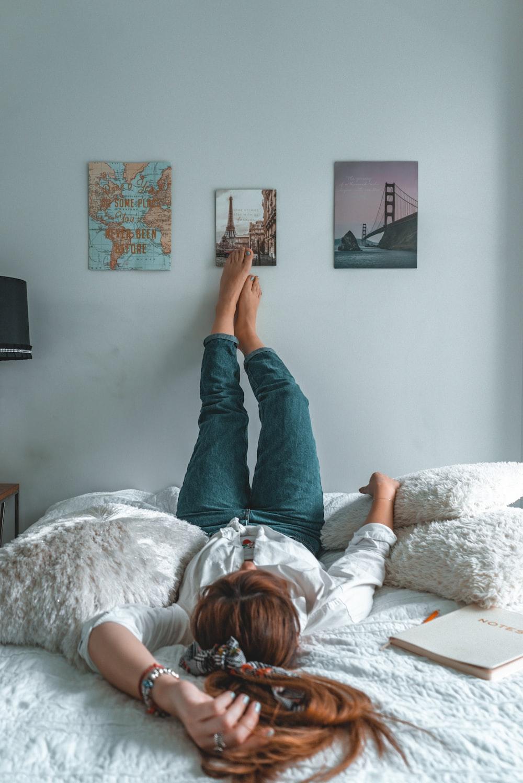 woman in blue denim jeans lying on bed