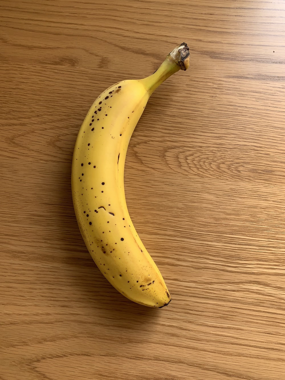 yellow banana fruit on brown wooden table