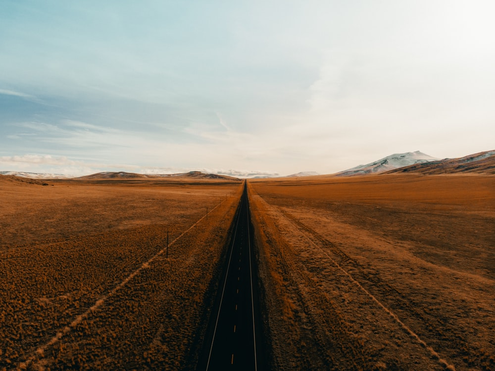 black metal train rail in the middle of brown field during daytime