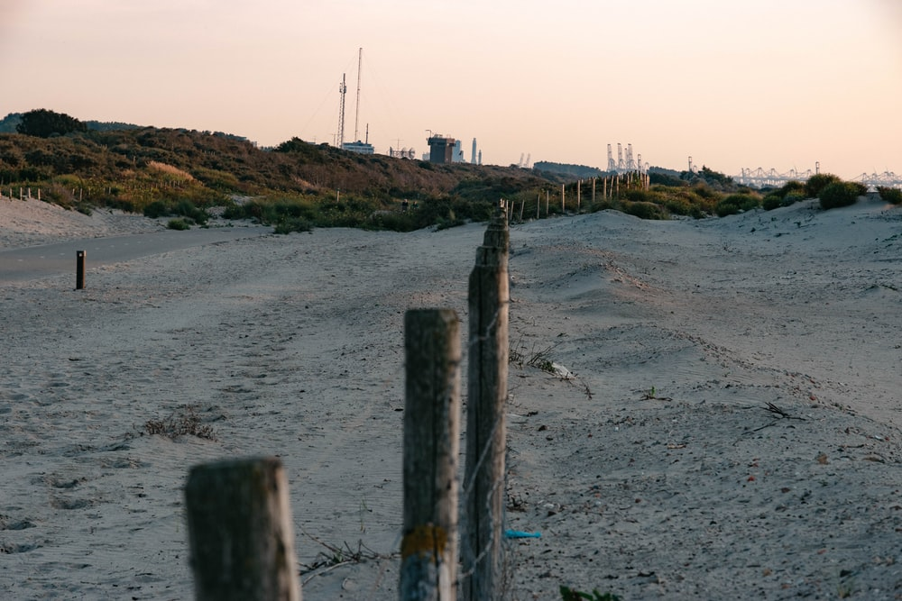 brown wooden fence on gray sand near body of water during daytime