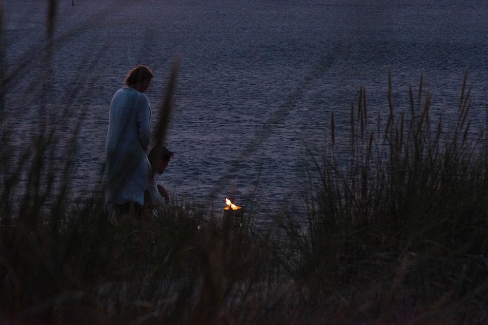 man in white shirt standing near body of water during daytime