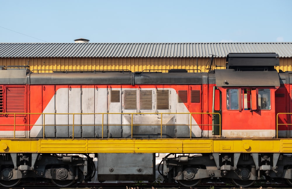 yellow and red train on rail tracks