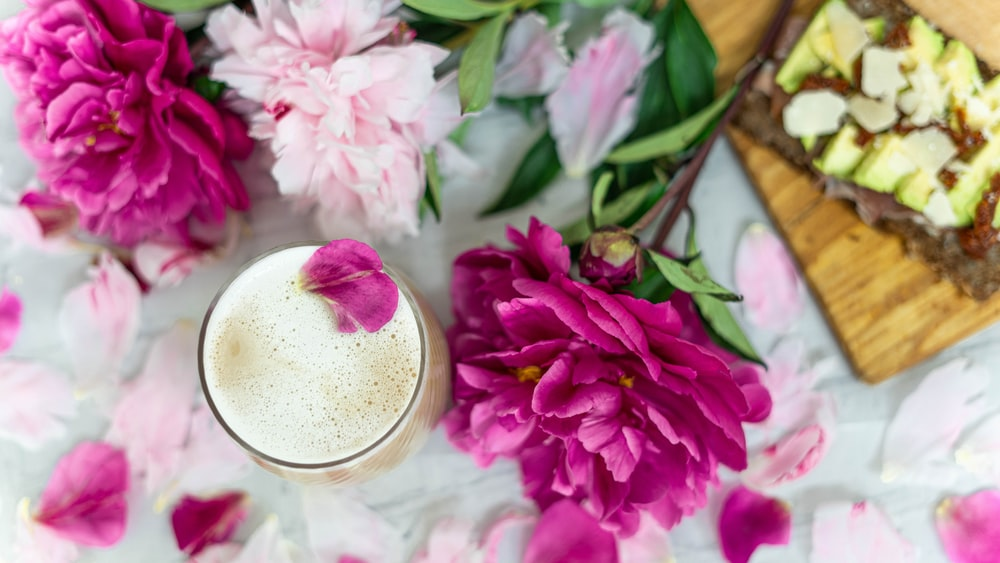 pink flowers beside clear drinking glass