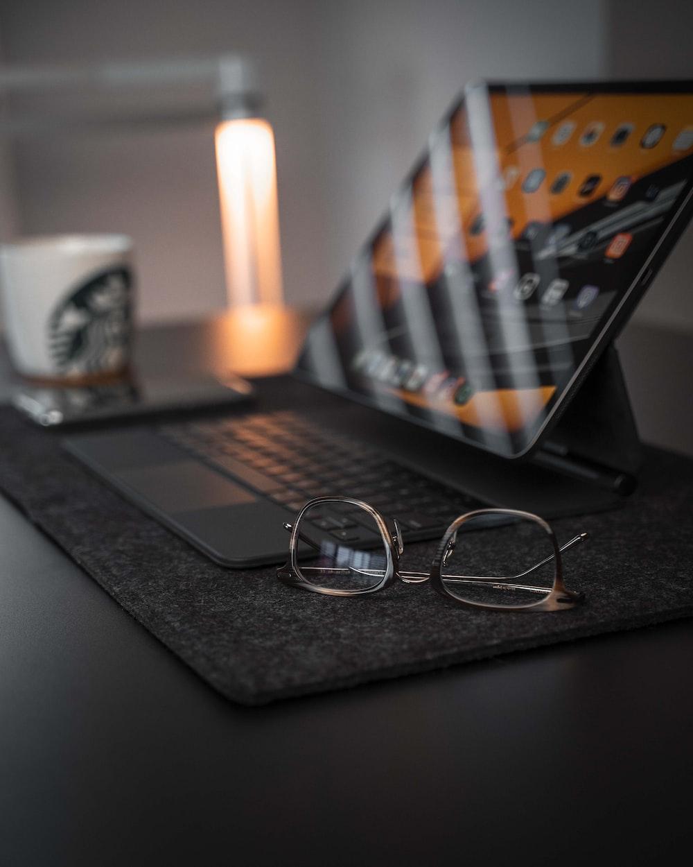 black framed eyeglasses on macbook pro