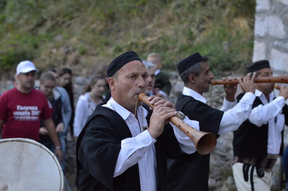 man in white dress shirt playing musical instrument