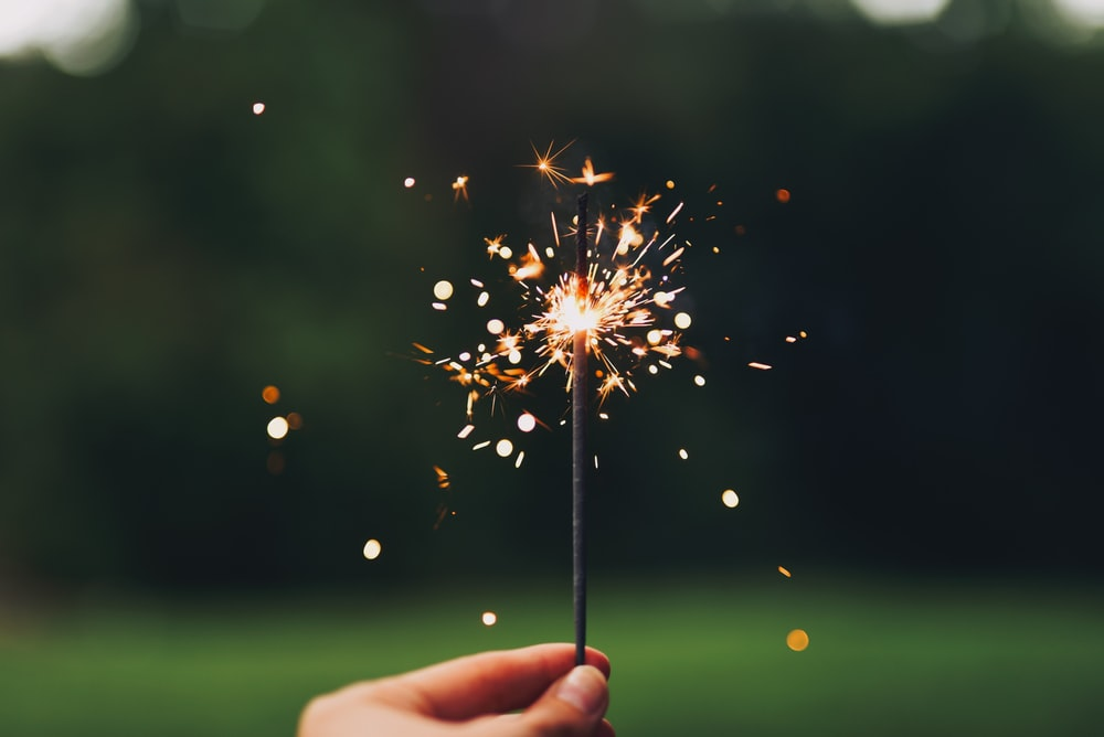 person holding sparkler with bokeh effect