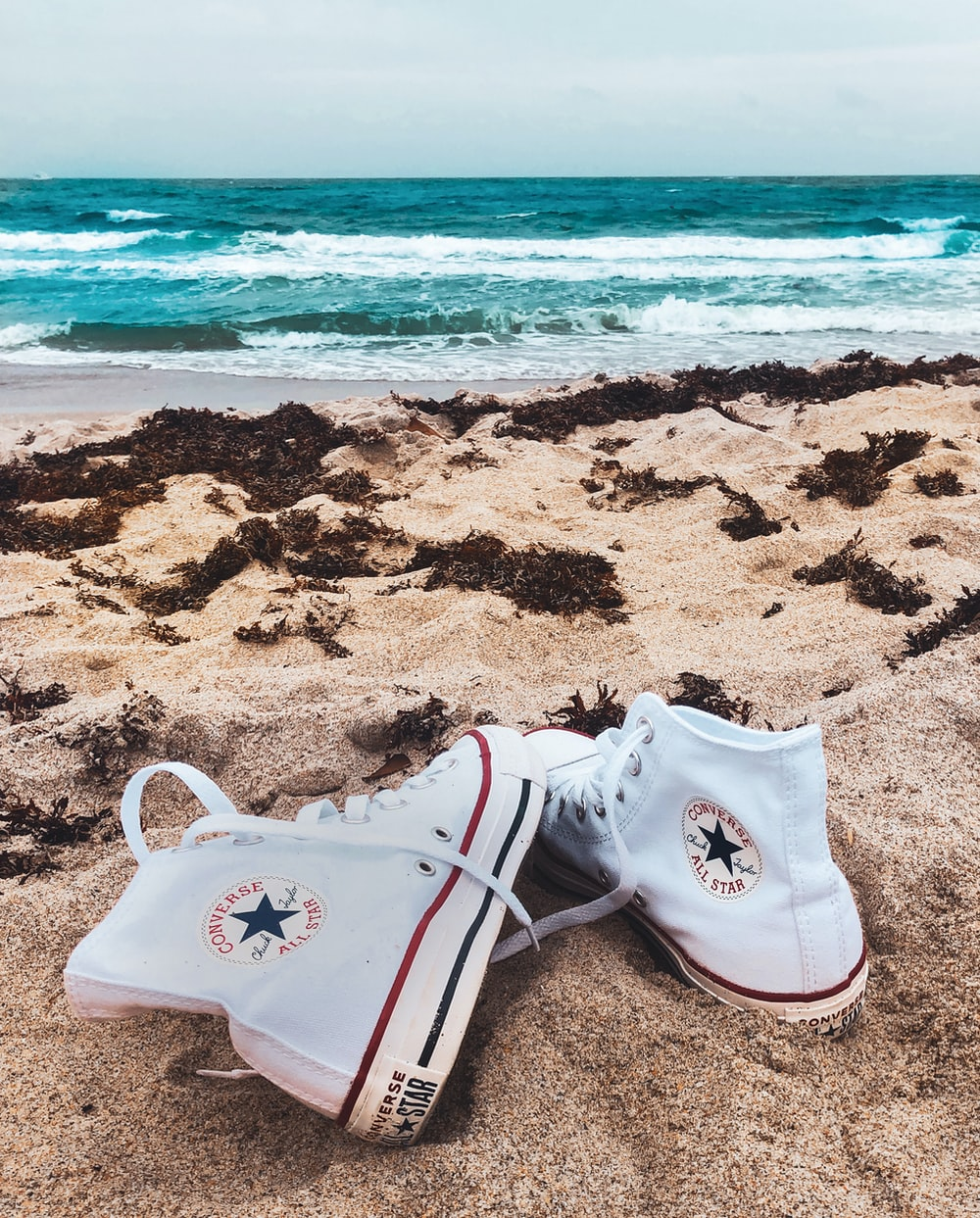white converse all star high top sneakers on beach shore