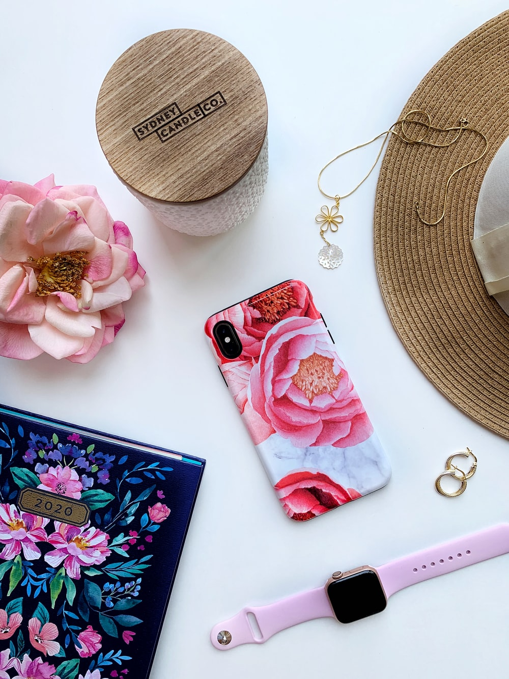 pink iphone case beside gold necklace