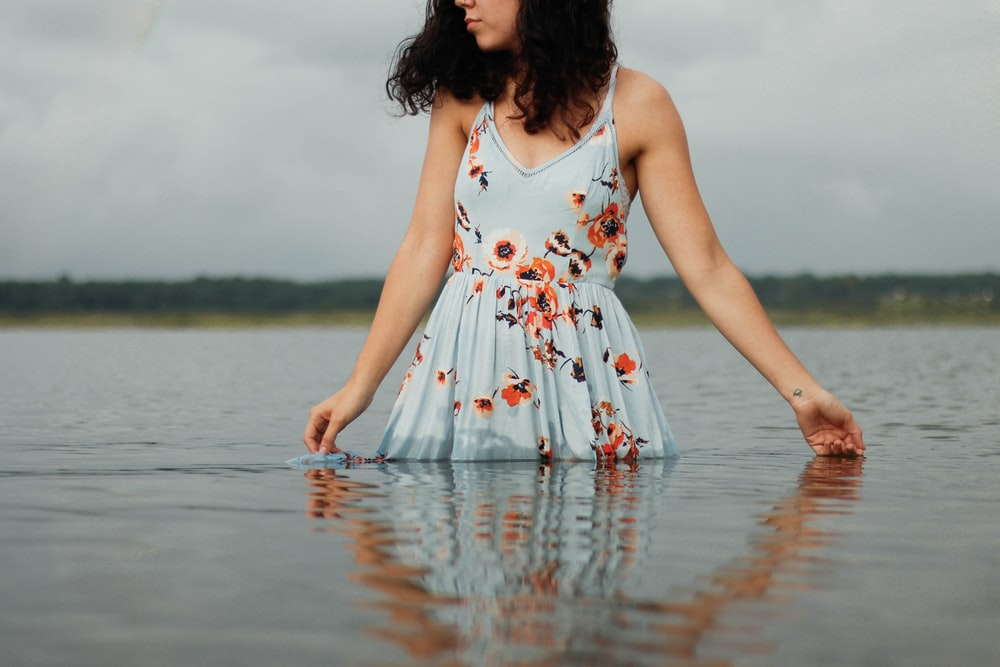 woman in white red and green floral dress standing on water during daytime