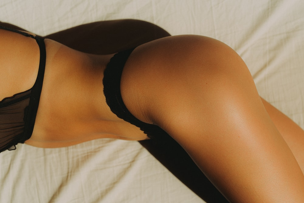 woman in black panty lying on white textile