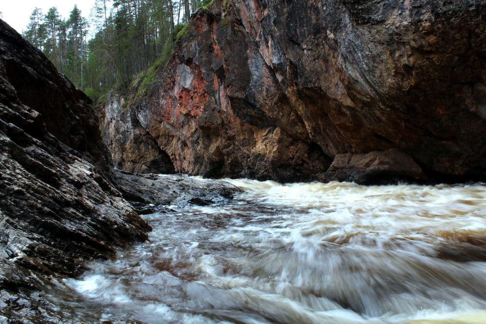 brown rocky mountain beside river during daytime