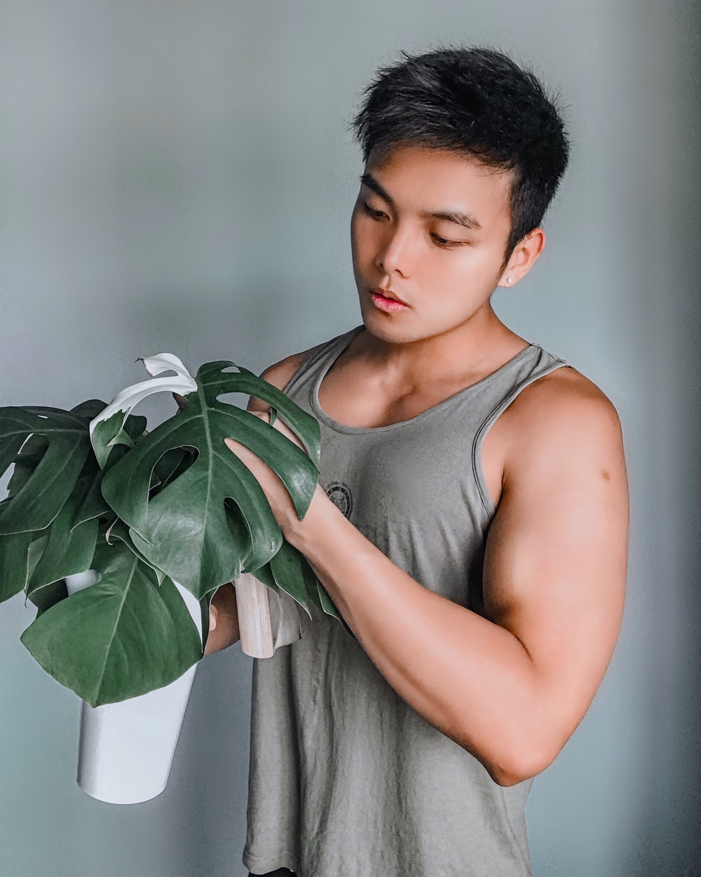 woman in gray tank top holding green plant