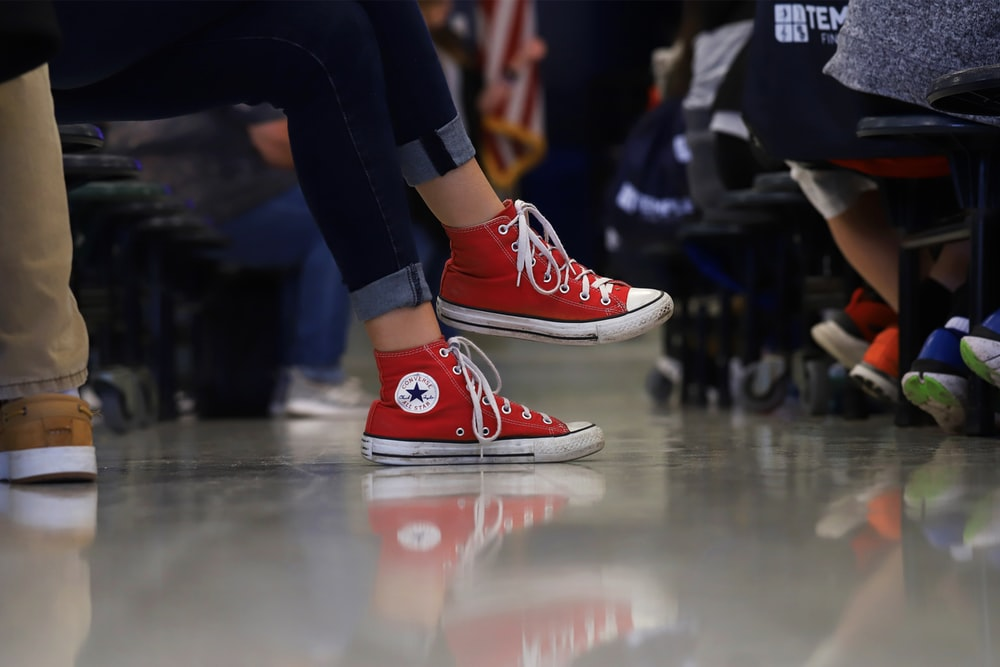 person in red and white converse all star high tops