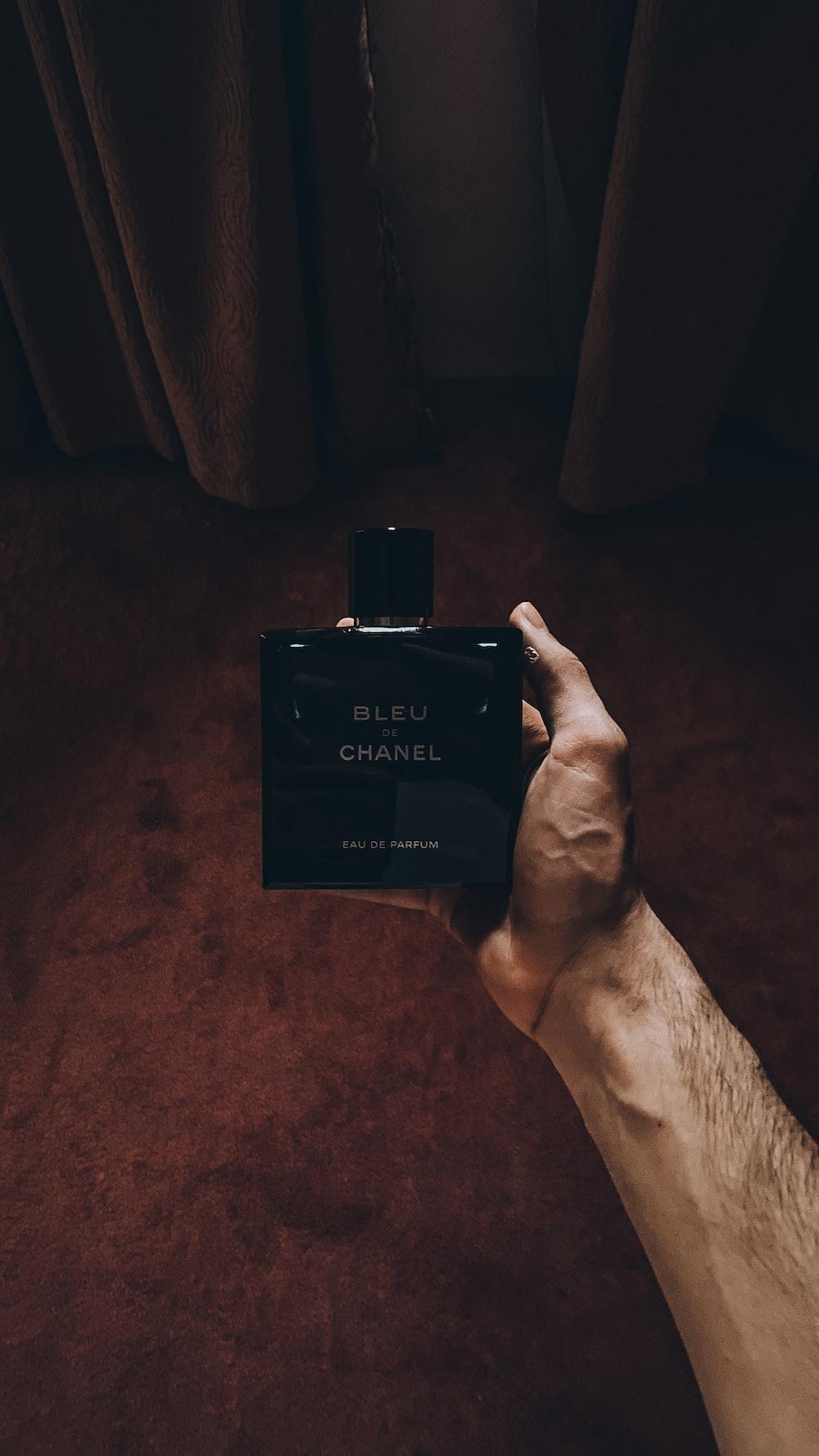 person holding black calvin klein perfume bottle