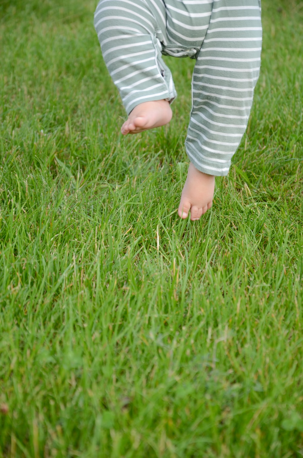 child in white and blue striped long sleeve shirt standing on green grass field during daytime