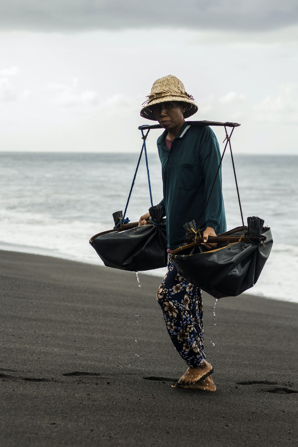 woman in blue jacket and black and white floral pants wearing brown hat standing on beach