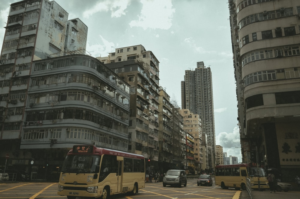 yellow bus on road near high rise buildings during daytime