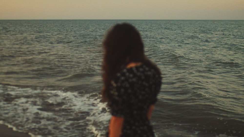 woman in black and white floral shirt standing on seashore during daytime