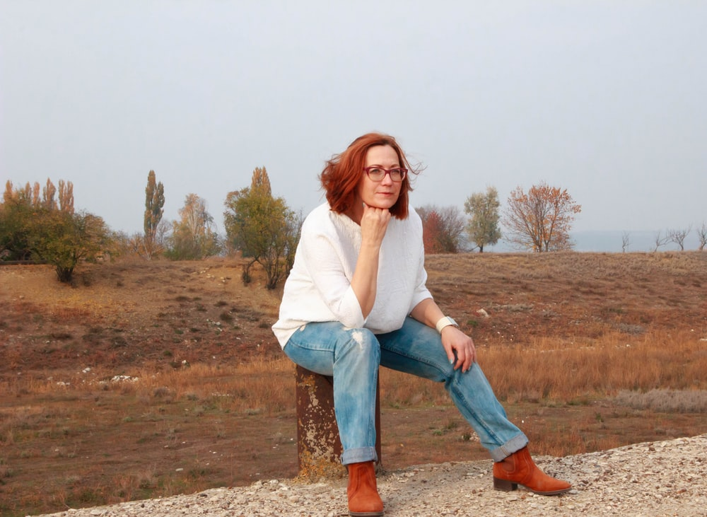 woman in white long sleeve shirt and blue denim jeans standing on brown field during daytime