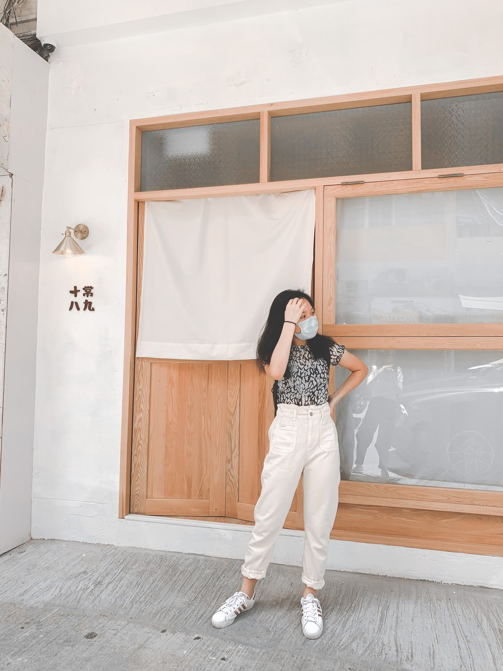 woman in black and white polka dot shirt and white pants standing beside brown wooden door