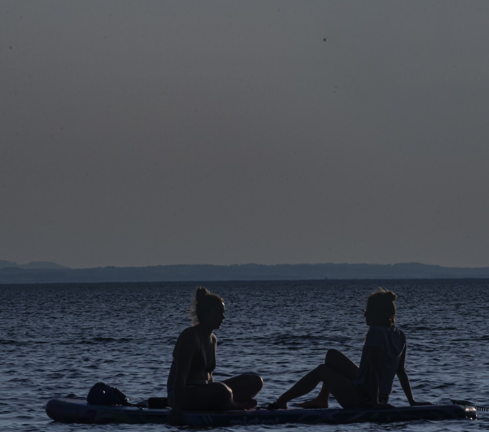 silhouette of people sitting on rock in the sea during daytime