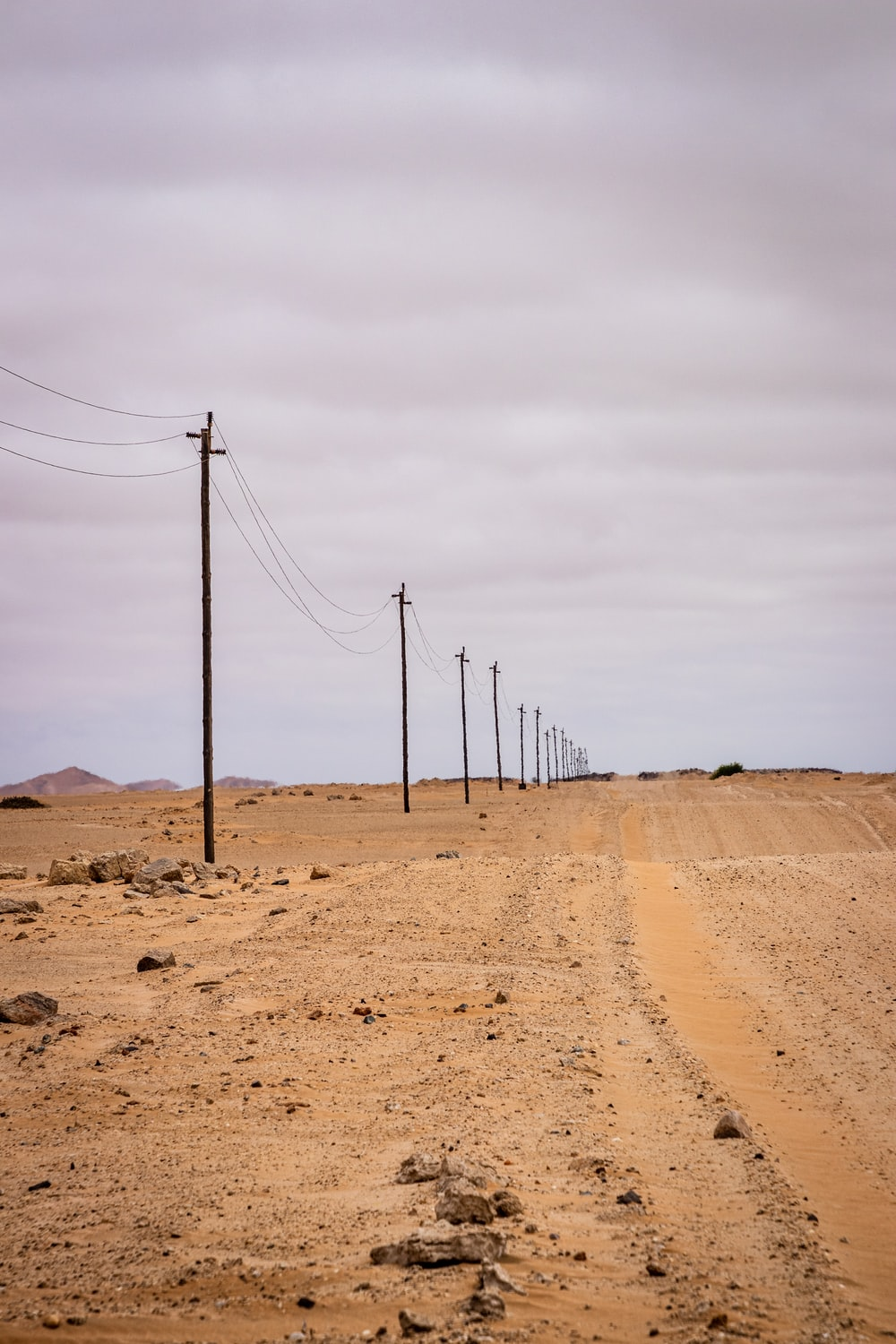 brown wooden electric posts on brown sand under white sky during daytime