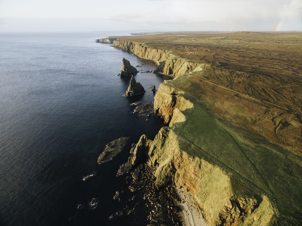 aerial view of green and brown mountain beside sea during daytime