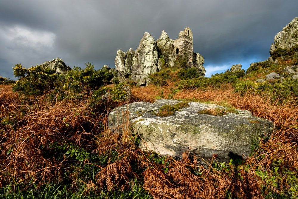 gray rock formation on green grass field under gray cloudy sky during daytime