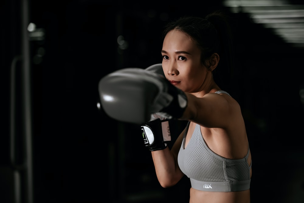 woman in white sports bra and black boxing gloves