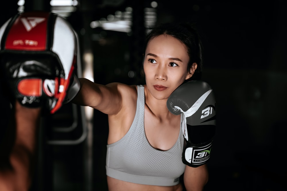 woman in gray sports bra and black and white nike boxing gloves