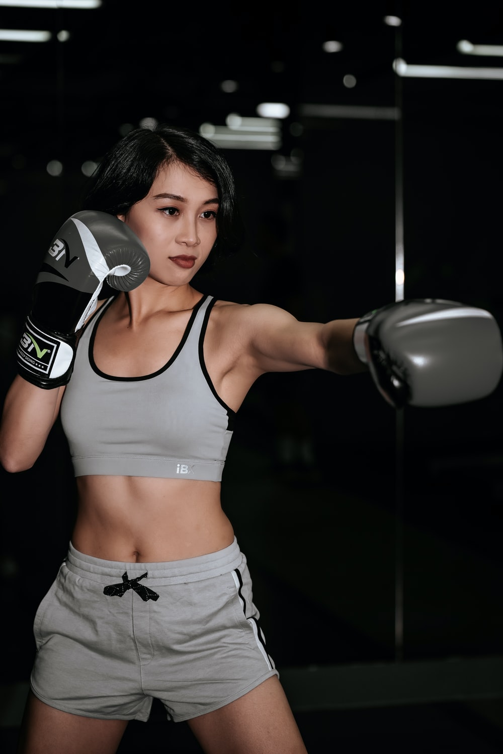 woman in white sports bra and white shorts holding black and white boxing gloves