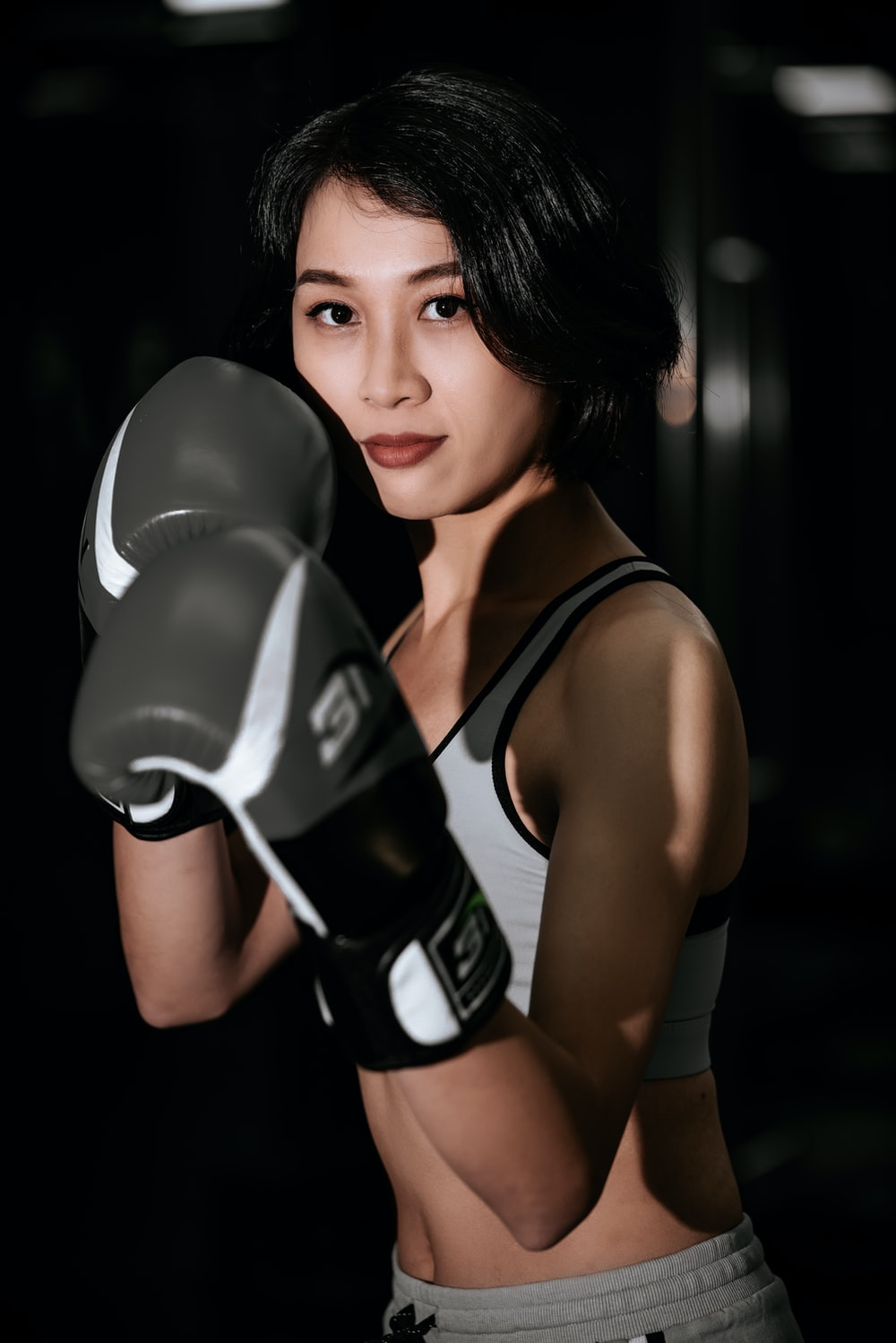 woman in black and white nike tank top wearing black boxing gloves