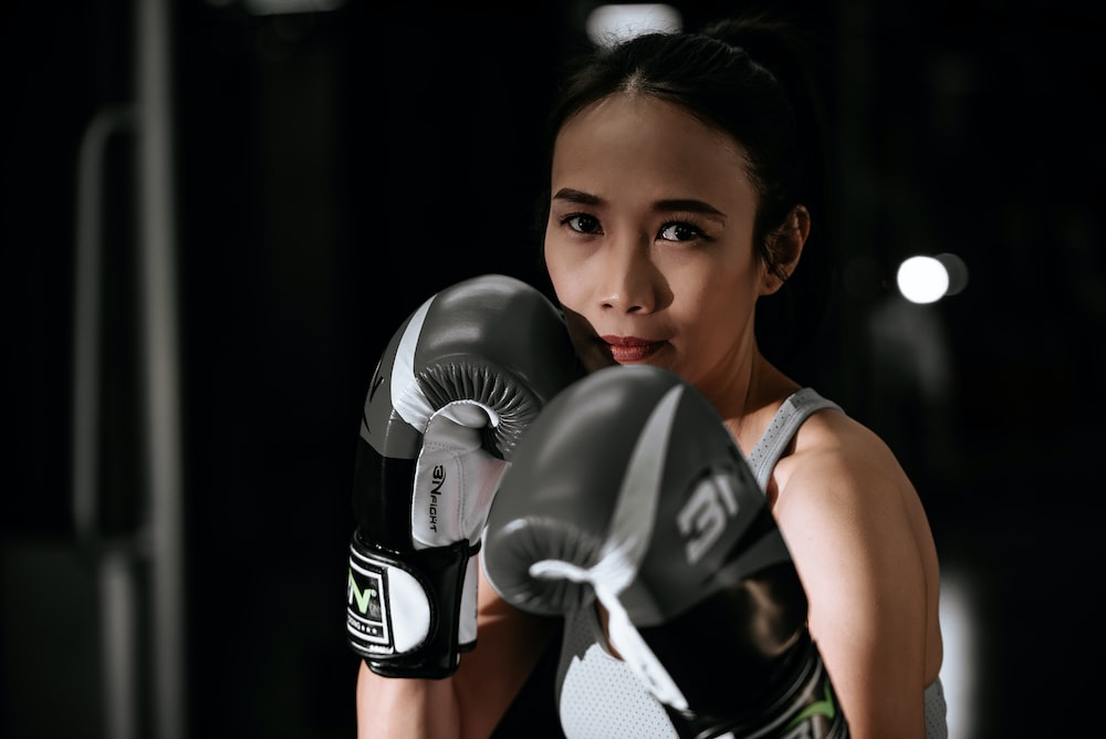 woman in black and white jersey shirt wearing black boxing gloves