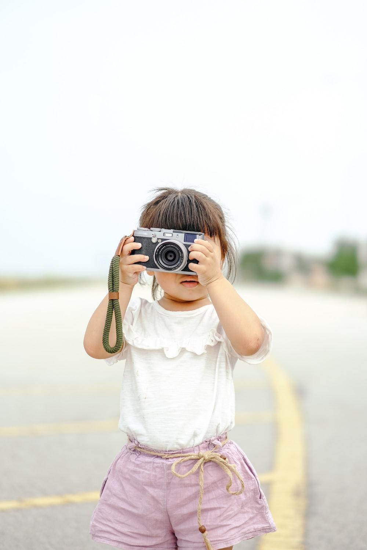 girl in white shirt holding black camera