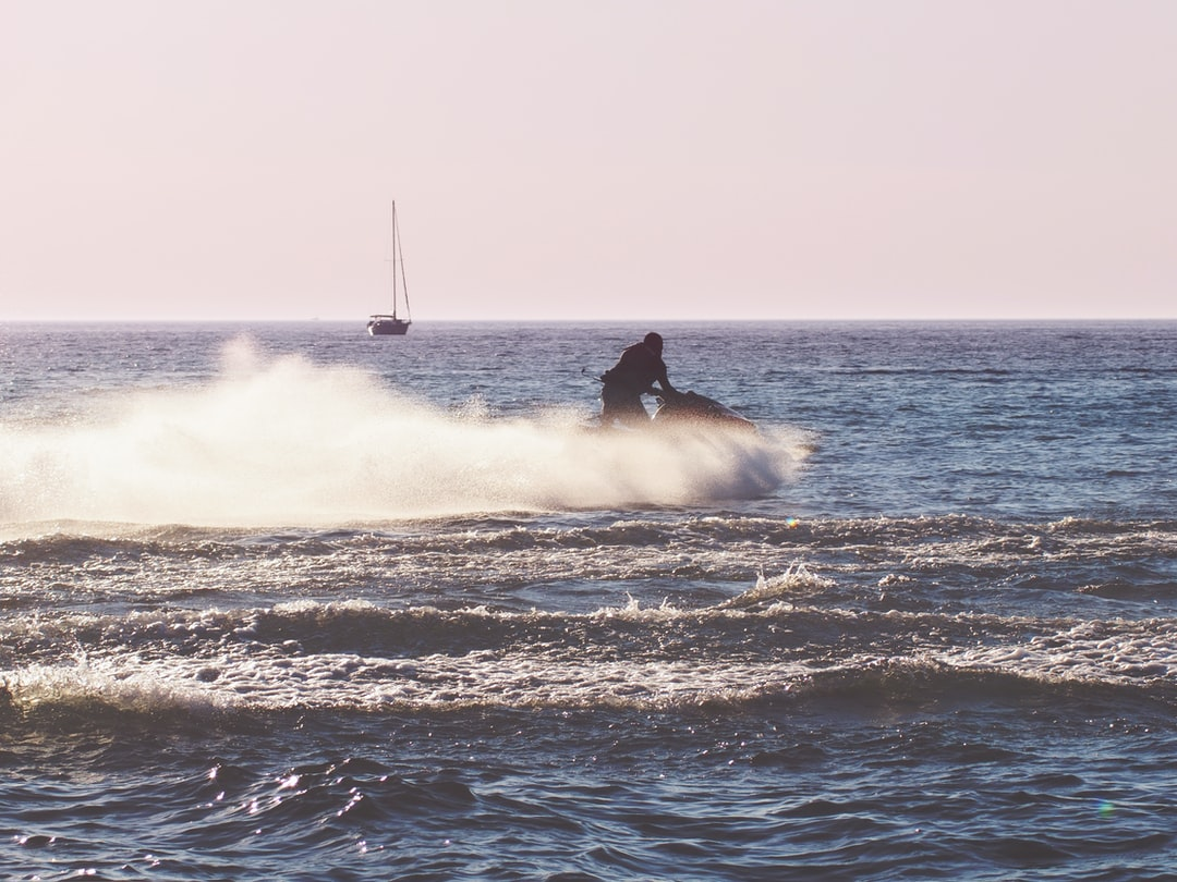 Person enjoying summertime on Lake Michigan driving a Sea-Doo with Sailboat in the background
