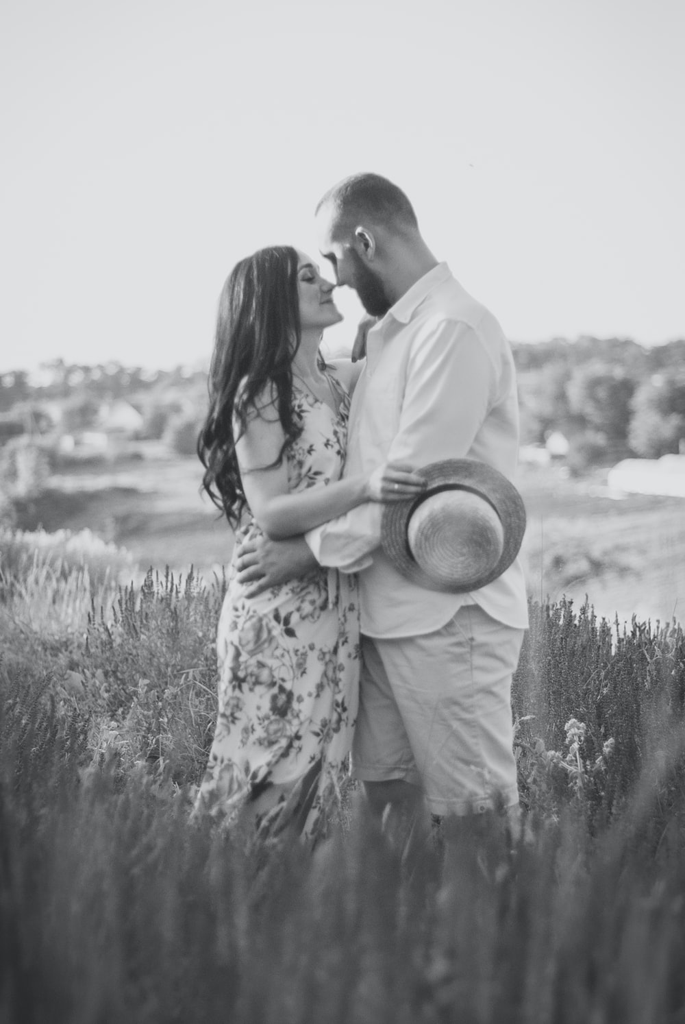 man and woman kissing on grass field in grayscale photography