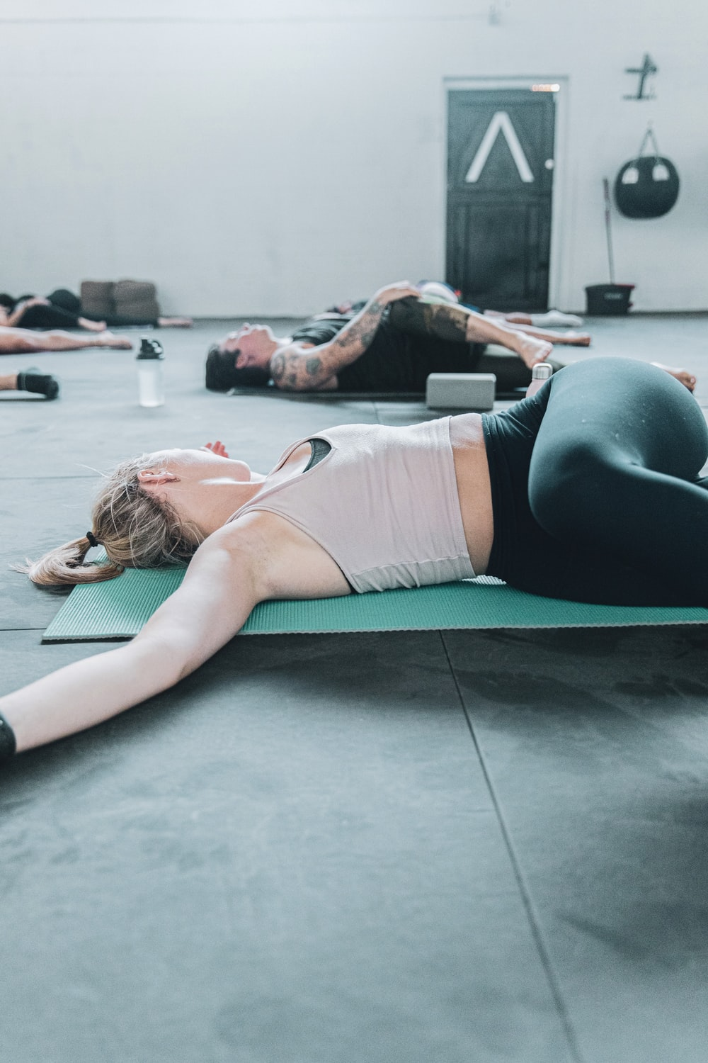 woman in white sports bra and black shorts lying on green yoga mat