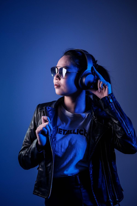 woman in black leather jacket wearing blue sunglasses