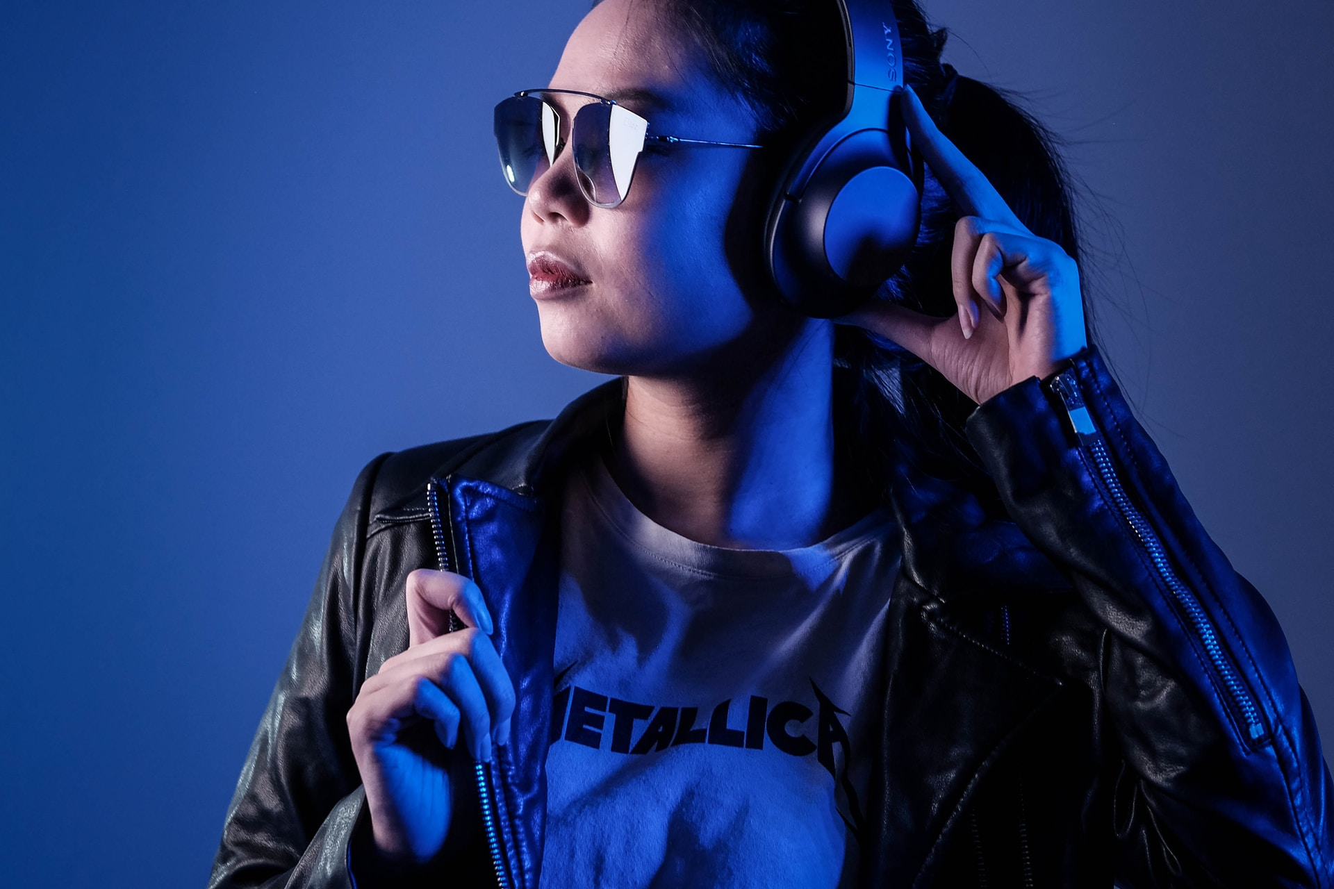 woman in black leather jacket wearing blue sunglasses