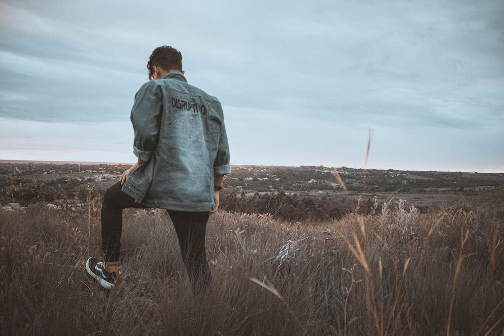 man in blue denim jacket standing on brown grass field during daytime