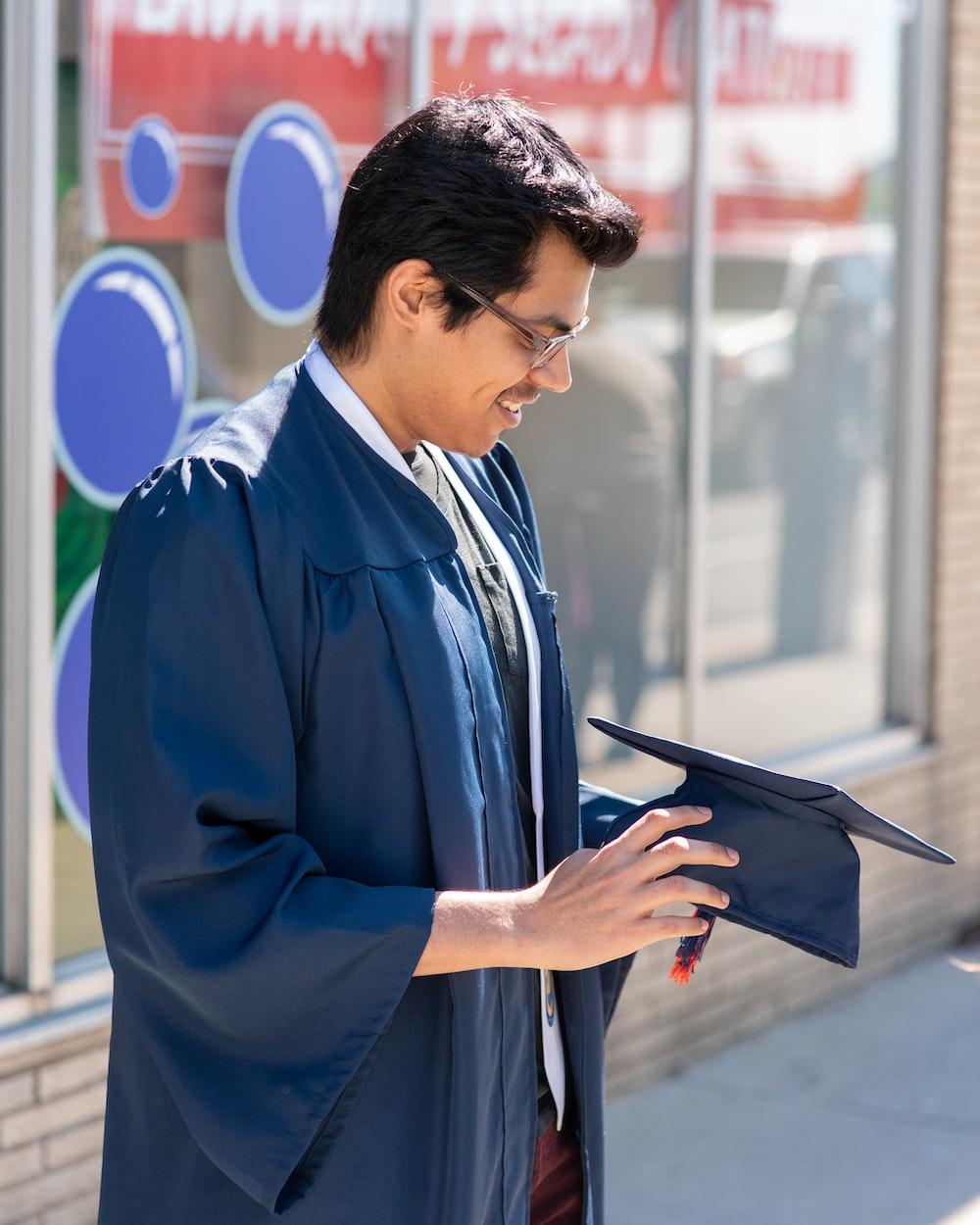 man in blue dress shirt holding black tablet computer