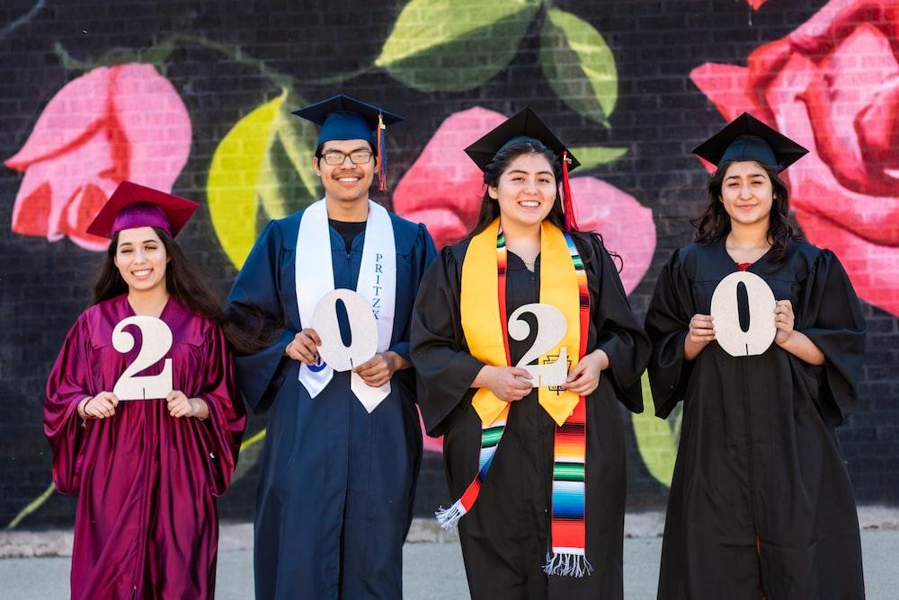 woman in blue academic dress standing beside woman in blue academic dress