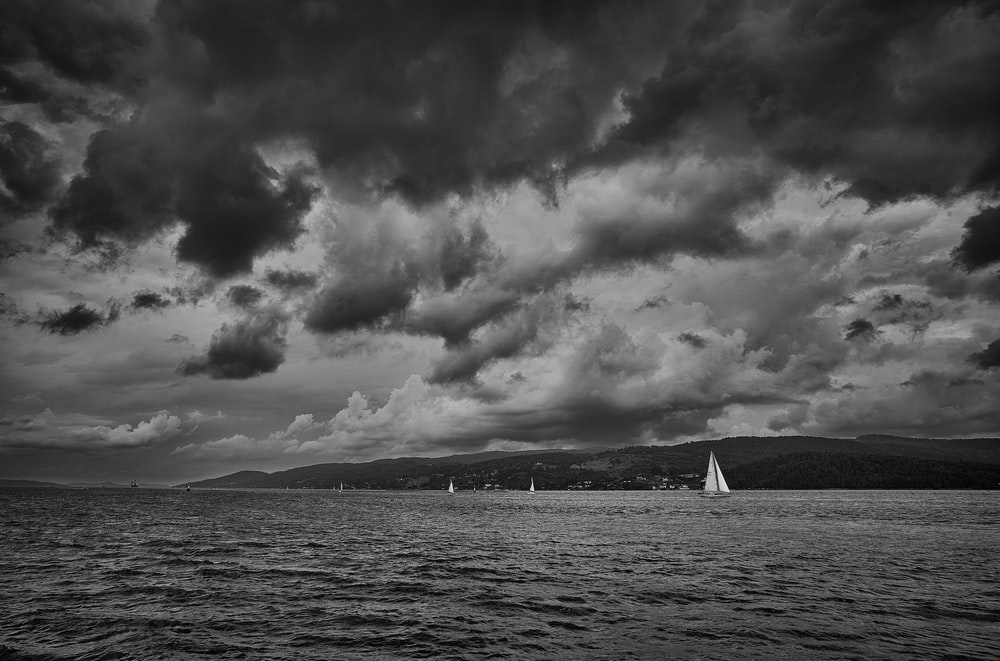 grayscale photo of sailboat on sea under cloudy sky